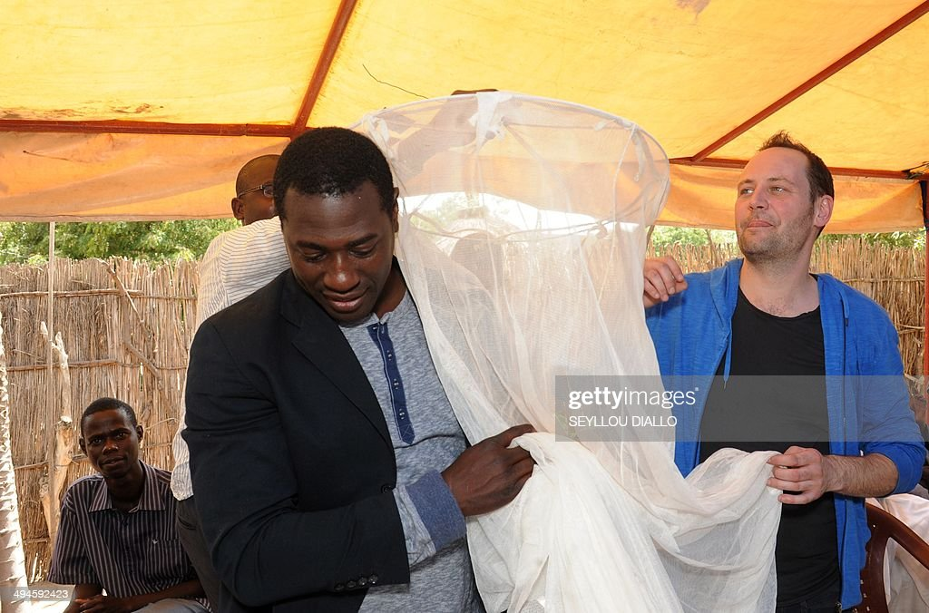 French-Burkinabe actor and slam poet Jacky Ido (L) and French actor, singer-songwriter and composer Christophe Mali (R) unfold a mosquito net during a visit of an health care centre on May 27, 2014 in the village of Keur Matabara, in the Senegalese region of Thies, as part of a tour organized by the Non-Governmental Organization (NGO) One.