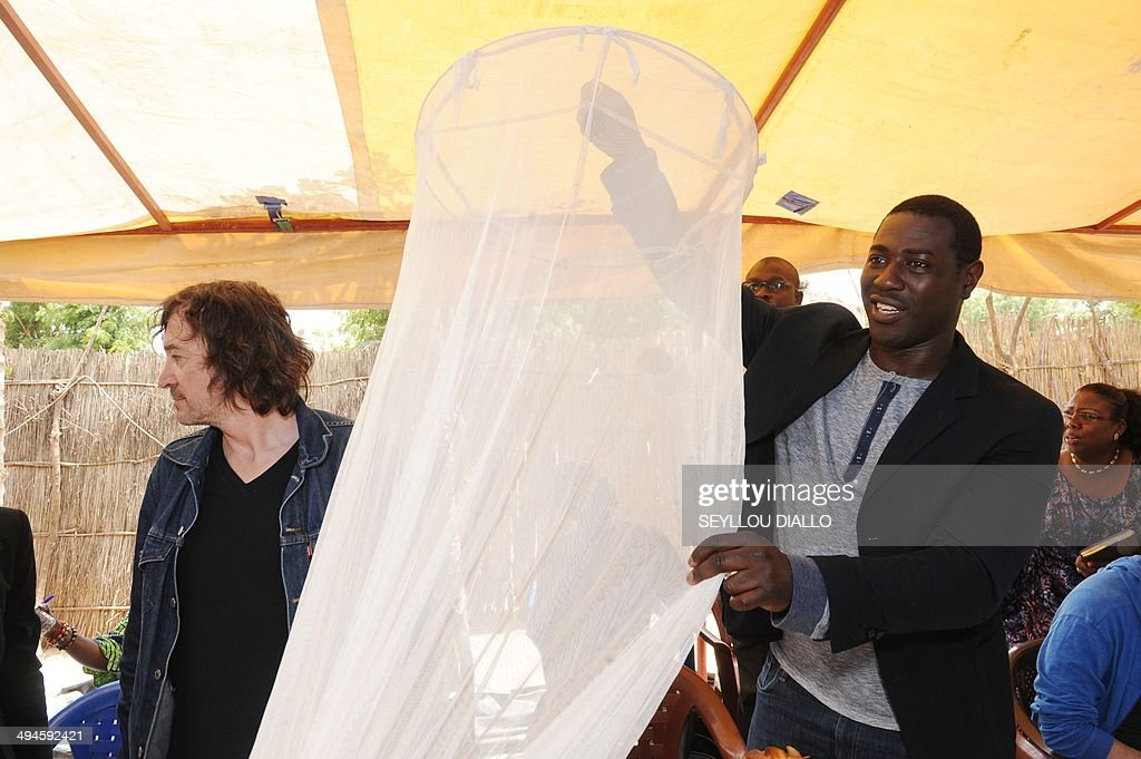 French-Burkinabe actor and slam poet Jacky Ido (R) holds a mosquito net beside French singer-songwriter and composer Cali (L) during a visit of an health care centre on May 27, 2014 in the village of Keur Matabara, in the Senegalese region of Thies, as part of a tour organized by the Non-Governmental Organization (NGO) One.