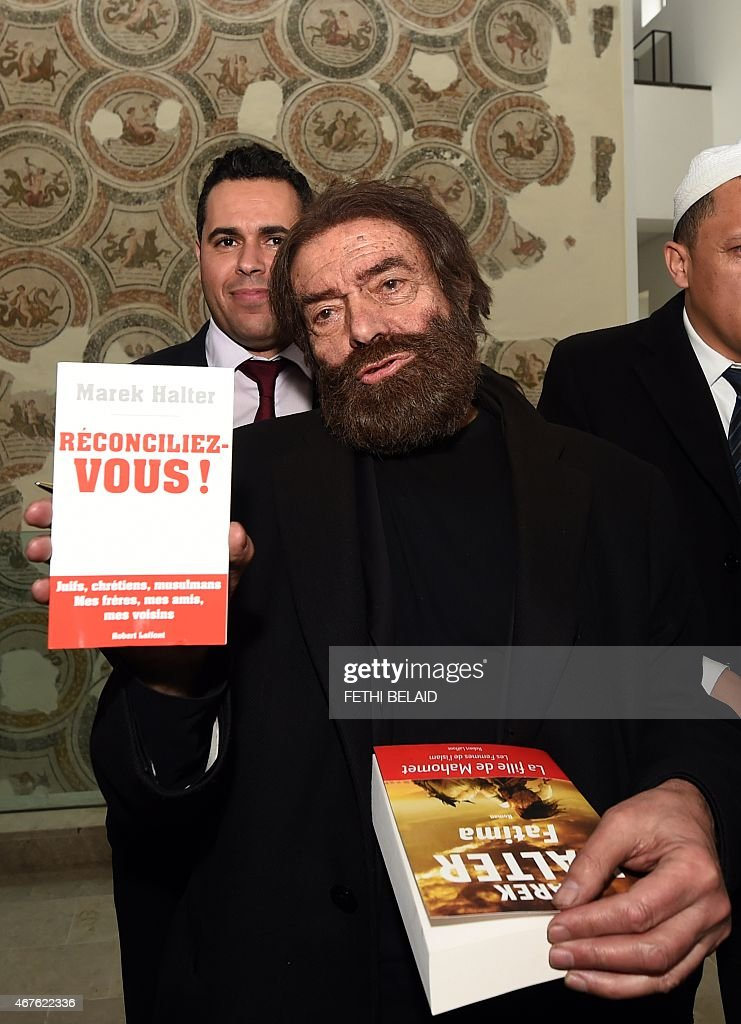 French-Jewish writer and activist <a gi-track='captionPersonalityLinkClicked' href=/galleries/search?phrase=Marek+Halter&family=editorial&specificpeople=768328 ng-click='$event.stopPropagation()'>Marek Halter</a> carries a copy of his book 'Reconciliez-Vous!' at the Bardo Museum in Tunis on March 26, 2015, during a visit to express solidarity with victims of the Tunis' museum attack. Tunisia said that it had arrested 23 suspects in connection with last week's jihadist massacre at the country's national museum.