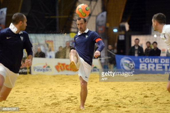 Mickael pagis shoots the ball during a friendly beach soccer match