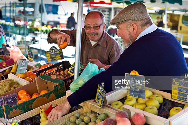 Frenchmen working on fruit staff at food market at Esplanade des Quais in La Reole Bordeaux region France