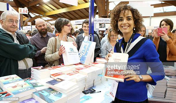 FrenchMoroccan writer Leila Slimani winner of France's Goncourt literary prize poses with her book 'Chanson Douce' on November 5 2016 during...