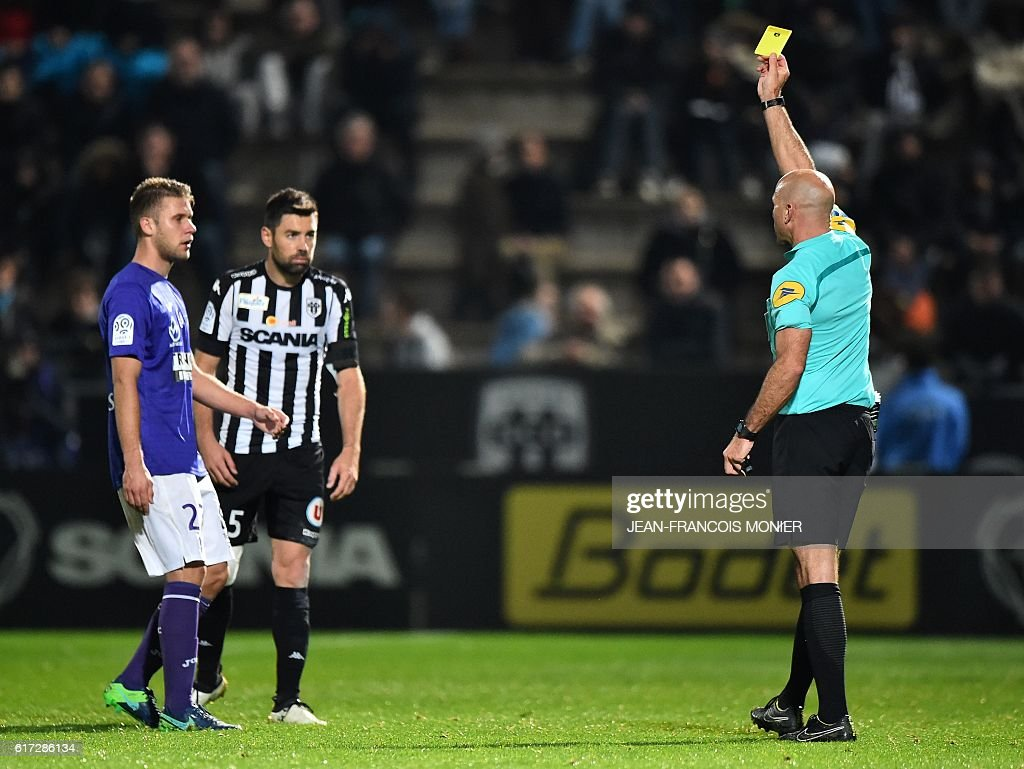 French's referee Bartolomeu Varela (R) gives a yellow card to Toulouse's French midfielder Alexis Blin (L) and Angers' French midfielder Thomas Mangani during the French L1 football match between Angers (SCO) and Toulouse (TFC) on October 22, 2016, at the Jean Bouin Stadium in Angers, northwestern France. / AFP / JEAN