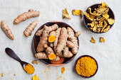 Fresh and dried turmeric roots in a wooden bowl. Grey textile background. Top view.