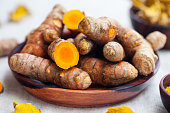 Fresh and dried turmeric roots in a wooden bowl. Grey textile background.