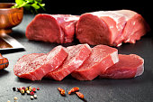 Fresh and raw meat. Sirloin medallions steaks in a row ready to cook. Background black blackboard