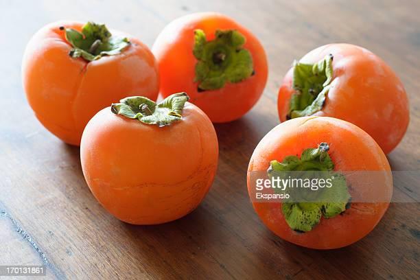 Persimmon frutta fresca e pomodori retroilluminazione sul vecchio tavolo di legno