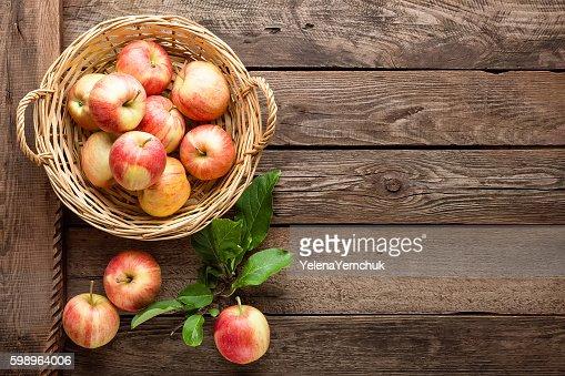 fresh apples in wicker basket on wooden table : Stock Photo