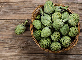 Artichokes with leaves in wicker basket with one on the surface in the foreground, on rustic wooden background. View from above.