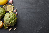Fresh artichokes with lemons and garlic on dark stone background, top view