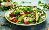 Fresh Avocado, shrimps salad with lettuce green mix, cherry tomatoes, herbs and olive oil, lemon dressing. healthy food.