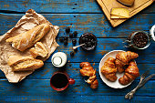 Fresh baked croissants and baguette, blackberry jam, coffee and cheese on old wooden table