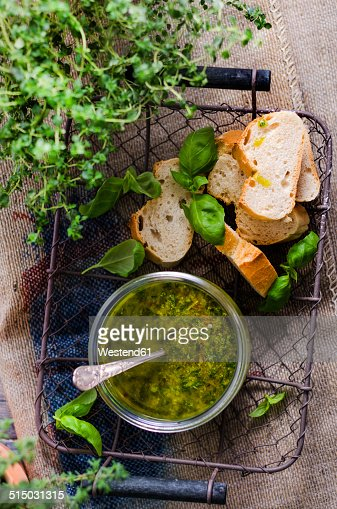 Fresh basil pesto in a glass and slices of baguette in a basket