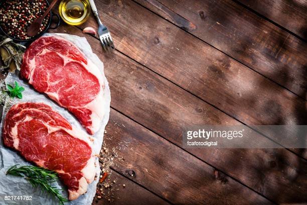 Fresh beef steak fillets with cooking abd seasoning ingredients on rustic wooden table