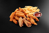 Fresh beer snacks chicken wings french fries cheese sticks assortment on black background