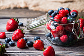 Berries in glass jar, over wooden background. Strawberries, Raspberries, Blueberry