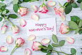 fresh rose and a white card with text happy valentines day on the vintage wooden background