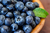 Fresh blueberries in wooden bowl. Shallow DOF.