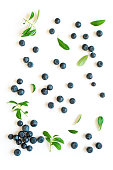 Fresh blueberries with green leaves leaves, organic blueberry pattern isolated on white background, top view.