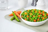 Fresh bowl of green beans and cubed carrots on white background