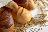 Close up of different kinds of bread mixed in a pile with wheat copyspace background layout food eating organic healthy ingredients dough bakery baking concept.