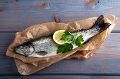 Fresh brook trout in baking paper on a wooden surface