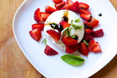 Fresh burrata cheese with strawberries, basil and balsamic syrup on white plate from above
