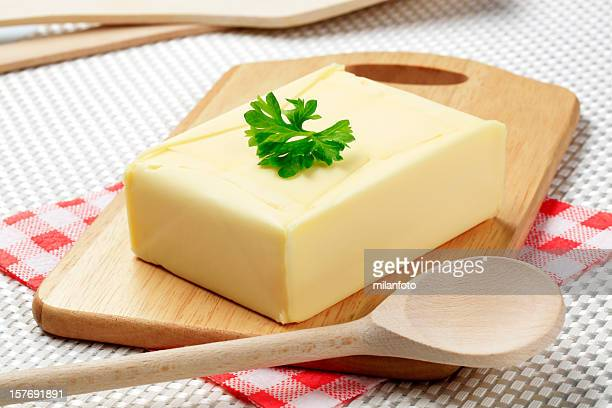 Fresh butter block on chopping board with a wooden spoon