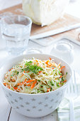 Fresh cabbage salad with carrots and cucumber in a white bowl, selective focus