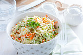 Fresh cabbage salad with carrots and cucumber in a white bowl, horizontal