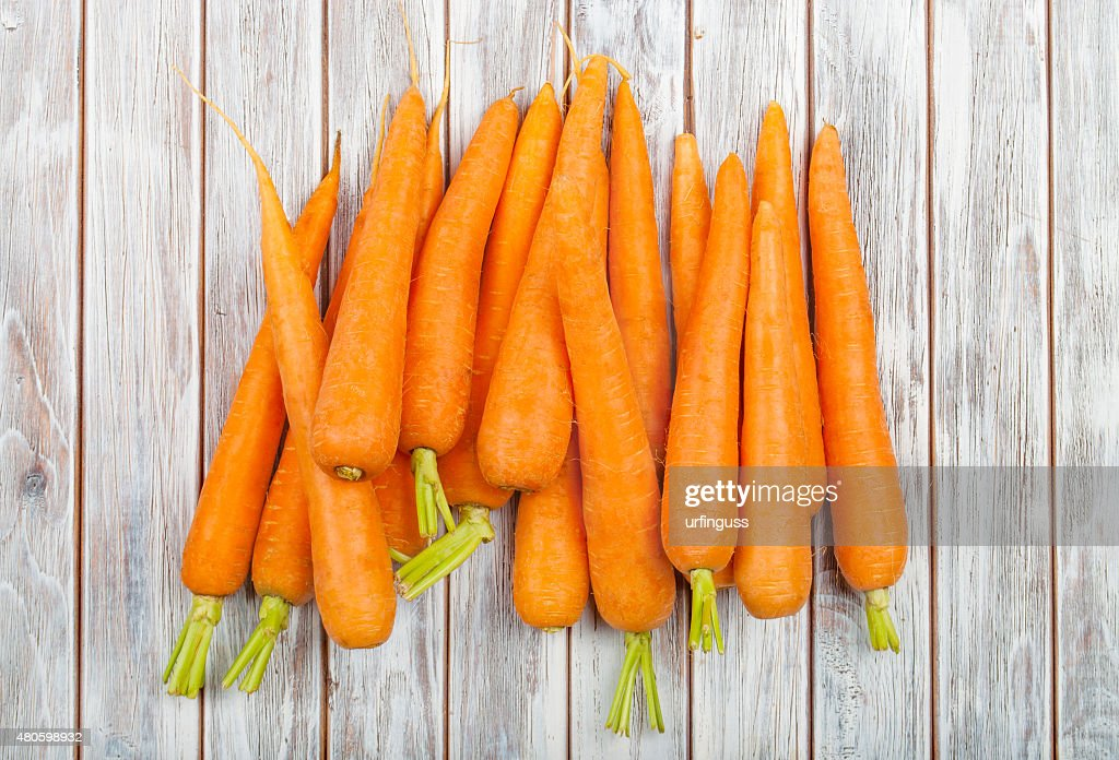 Fresh carrot isolated on wooden background : Stock Photo
