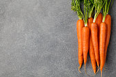 Fresh carrots bunch on a grey stone background Top view Copy space.
