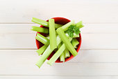 bowl of green celery stems on white wooden background