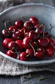 Fresh cherries in a metal dish