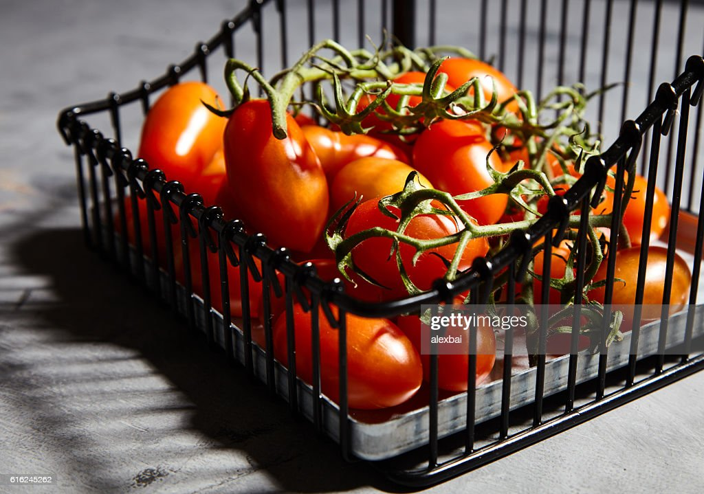 Fresh cherry tomatoes on branch in iron basket : Stock Photo
