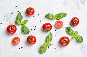 Fresh ripe red cherry tomatoes with basil leaves and black pepper on a stone table, vegetable pattern, top view