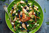 Fresh Chicken salad with Blueberries, feta, carrots, nuts and green vegetables. healthy food concept.