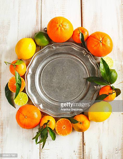 Fresh citrus fruits with leaves around empty vinta