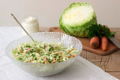 Fresh coleslaw salad in bowl and ingredients for salad. Rustic style, selective focus.