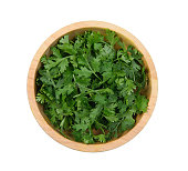 Top view of fresh coriander leaves in wooden bowl on white background.