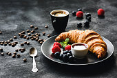 Fresh Croissant Berries and Coffee Cup On Black Background. Continental Breakfast. Coffee Break.