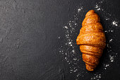 Fresh croissant on a black slate background. Top view Copy space