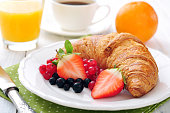 Fresh croissant with berries, coffee and orange juice closeup
