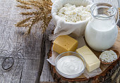 Fresh dairy products (milk, cottage cheese, cheese, butter, sour cream), wheat, rustic wood background