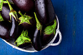 Fresh eggplant in grey basket on blue wooden table.Rustic background. Top view. Copy space. Vegan vegetable