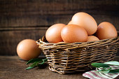 Fresh eggs in a rustic willow basket against dark wooden background