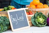 "Fresh farmers market veggies with ""buy local"" chalkboard sign"