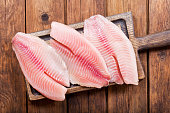 fresh fish fillet on wooden board, top view