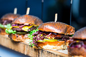 Close up image of a selection of freshly flame grilled burgers in a row on a wooden counter at Borough Market, one of the oldest and most famous food markets in the world. Each of the burgers has its
