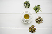 Fresh fragrant and healthy herbal tea in a glass or mug on a white wooden surface. Next to it lie various dried herbs for making tea. Healthy product.